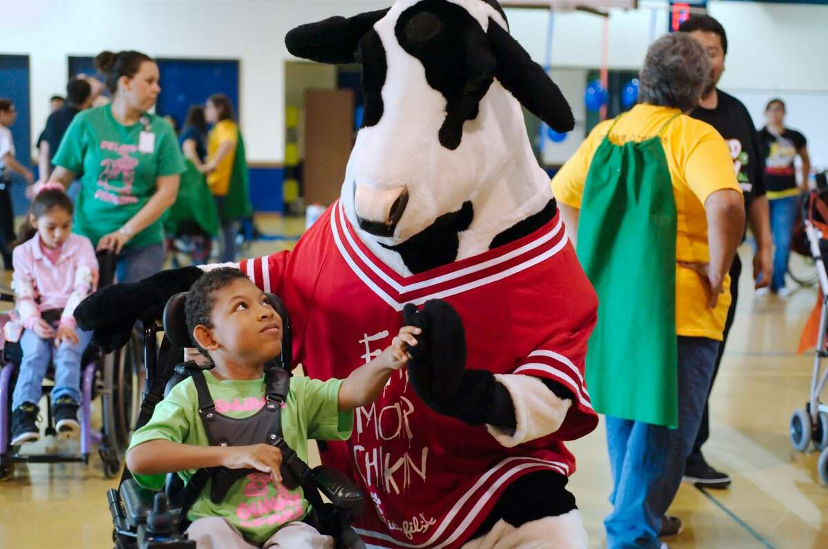 Syr Walker gets a high five from the Chick-fil-A cow during the Motor Activity Training Program field day at the Verne Cox center in 2016. The center is offering programs during the pandemic, but its participants say they miss in-person contact from events such as these.