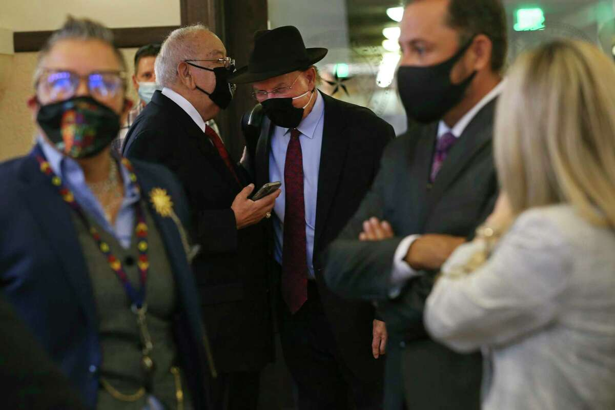 Bexar County Judge Nelson Wolff, center right, talks with Bexar County Courts Administrative Judge John A. Longoria before a press conference on Friday. Bexar County District Attorney Joe Gonzales and Wolff announced the addition of more judges to handle domestic violence cases.