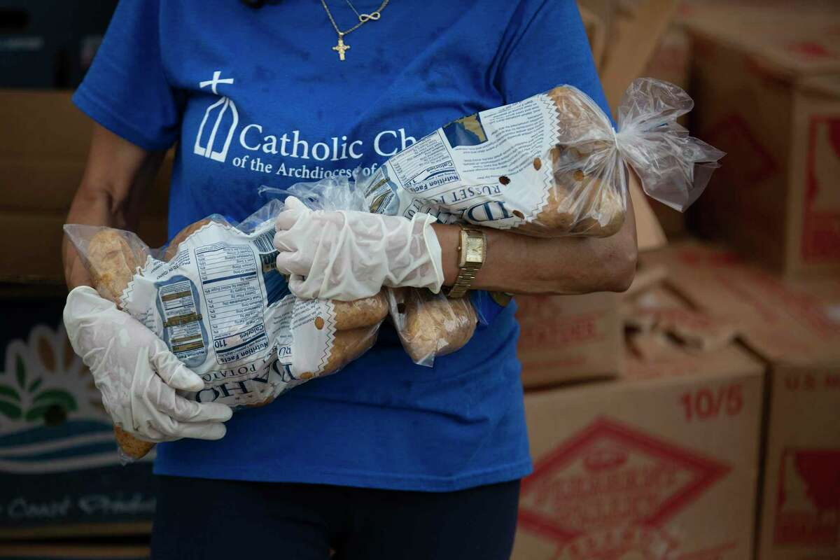 Carol Herrera, a volunteer at Catholic Charities of the Archdiocese of Galveston-Houston, helps distribute food as part of the organization's food-pantry program.