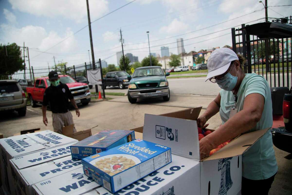 Catholic Charities' Dhyaa Yousif, left, and Toni Romero prepare packaged food for distribution. Besides food aid, the group provides rental and utility-bill assistance.