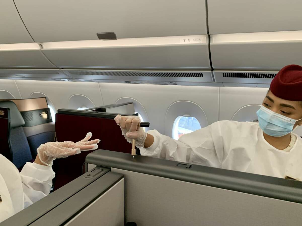Flight attendants crank the special brass key that transforms seats into double beds on a Qatar Airways Airbus A350 similar to the one that will fly between San Francisco and Doha.
