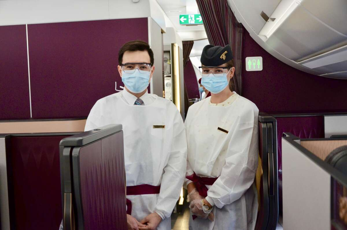 Qatar Airways cabin crew members don their protective gowns and safety gear in the business class cabin.