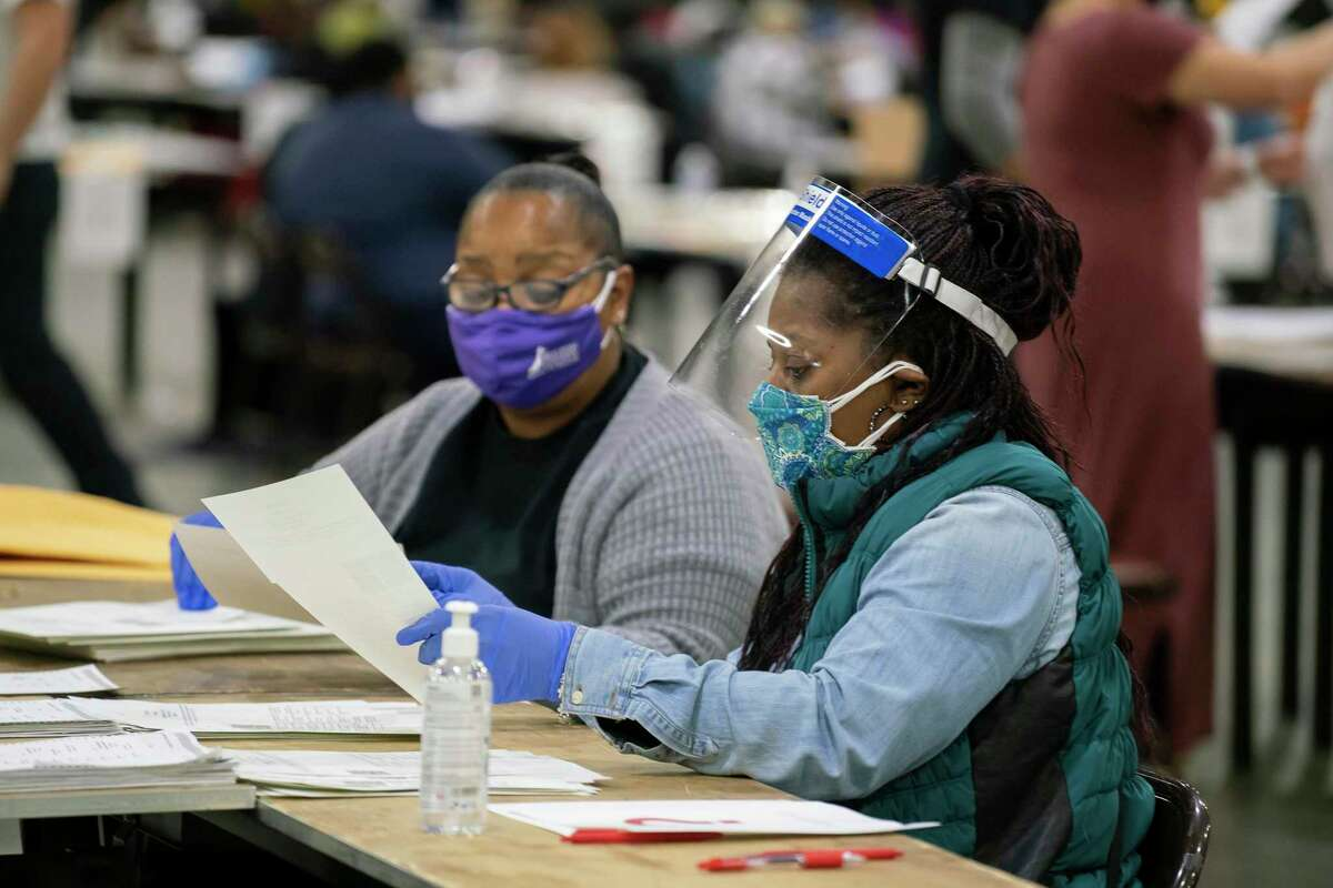 Workers recount election ballots by hand at the Georgia World Congress Center in Atlanta on Saturday. Some readers say let the recounts and legal challenges play out.