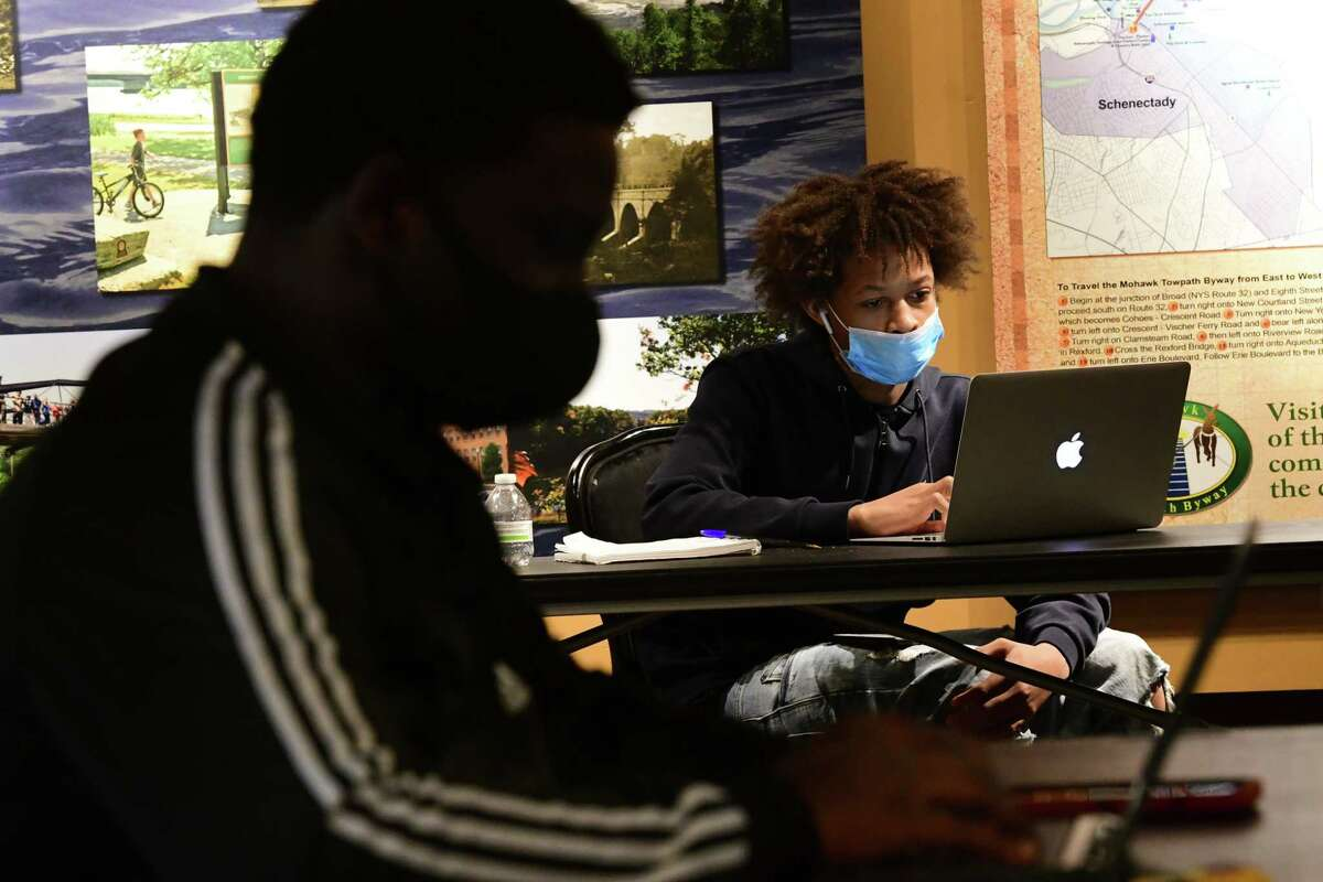 Bilal Allen, 16, of Schenectady, right, works on a computer as the Bridge the Gap program is held in the Robb Alley of Proctors on Friday, Nov. 20, 2020 in Schenectady, N.Y. (Lori Van Buren/Times Union)