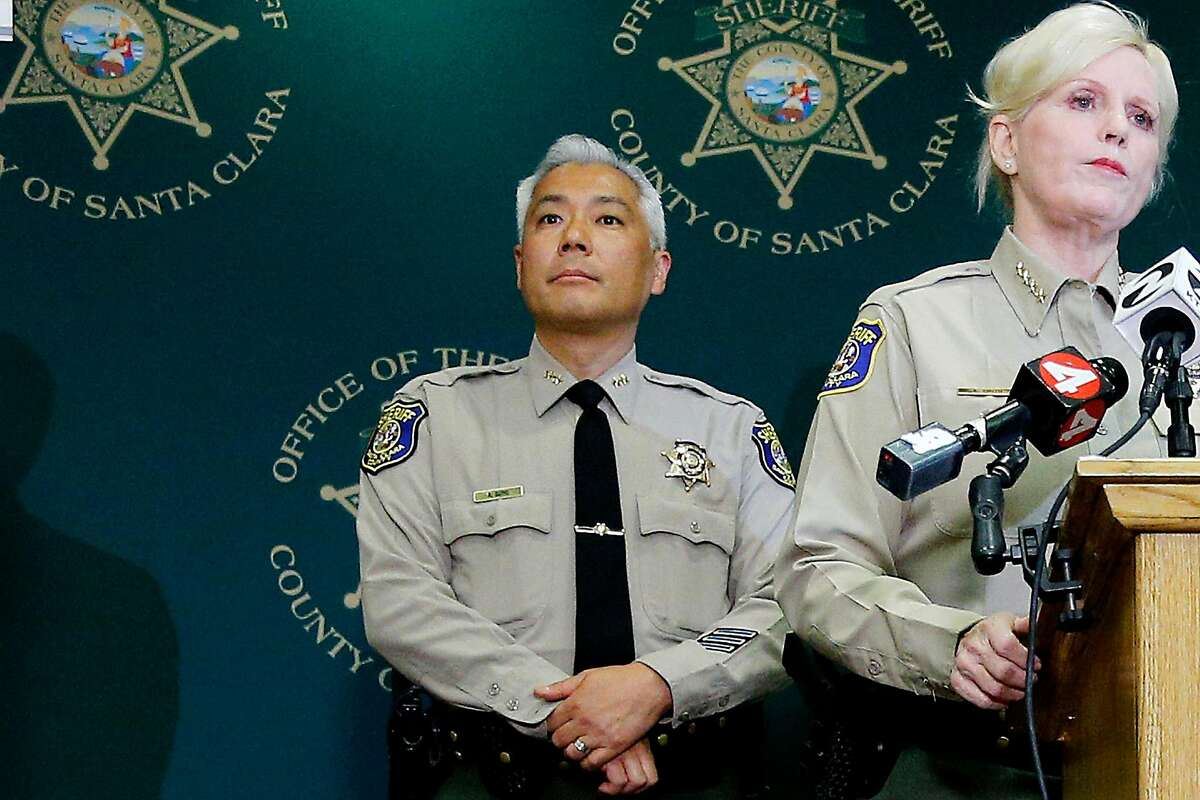 Santa Clara County Undersheriff Rick Sung stands behind Sheriff Laurie Smith at a news conference.