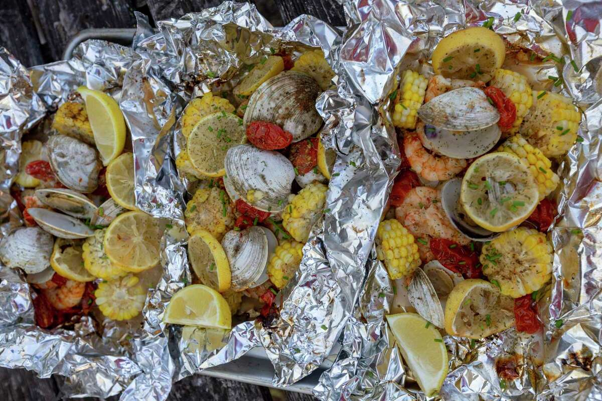 Finished seafood foil packs with clams, scallops and shrimp come off the grill at Chuck's Food Shack.