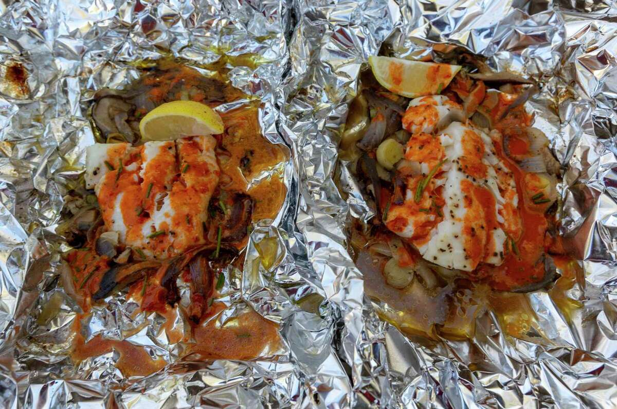 Finished mix-and-match seafood foil packets that contain cod, leeks, mushrooms, scallions and red onion.