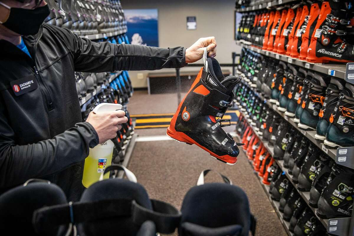 Zachary Kordal sprays disinfectant on rental ski boots during opening day at Heavenly Mountain Resort in South Lake Tahoe, California, November 20, 2020.
