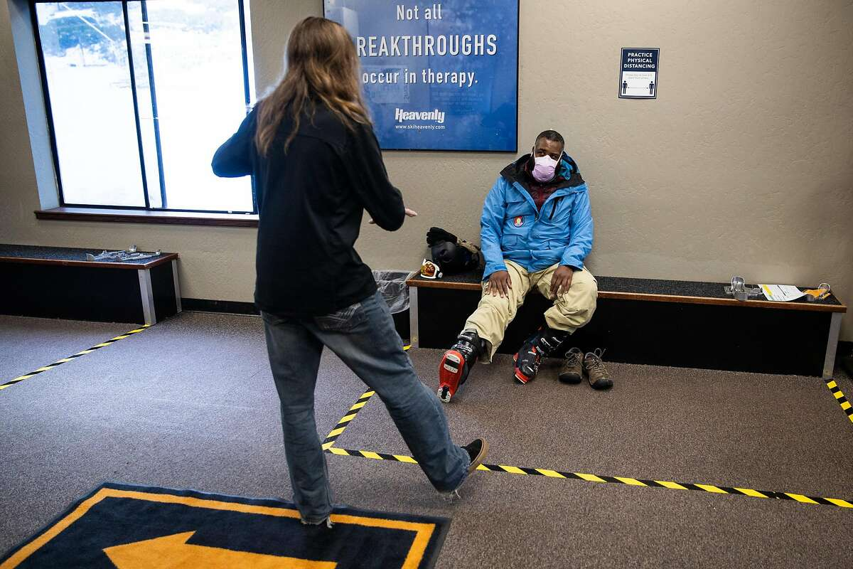 Rohlando Aaron of Fremont gets some socially distant help fitting rental ski boots on opening day at Heavenly Mountain Resort in South Lake Tahoe, California, November 20, 2020.