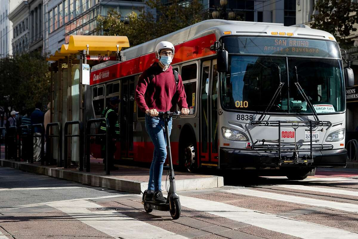 A person on a scooter move past a bus near 4th and Market street in San Francisco, Calif. Friday, October 30, 2020. The Department of Public Works and the San Francisco Municipal Transportation Authority has been quietly telling stakeholders the past couple weeks that due to budget cutbacks, bicycles will now share a lane along with taxis, paratransit, and commercial vehicles, and Muni busses will use only the center lane instead of curbside stops. The city will save $40 million, but it will still cost $121 million and an additional $7 million for redesign. The plane came to a head at a meeting Tuesday, with city supervisors and bike and pedestrian advocates protesting the sudden change.