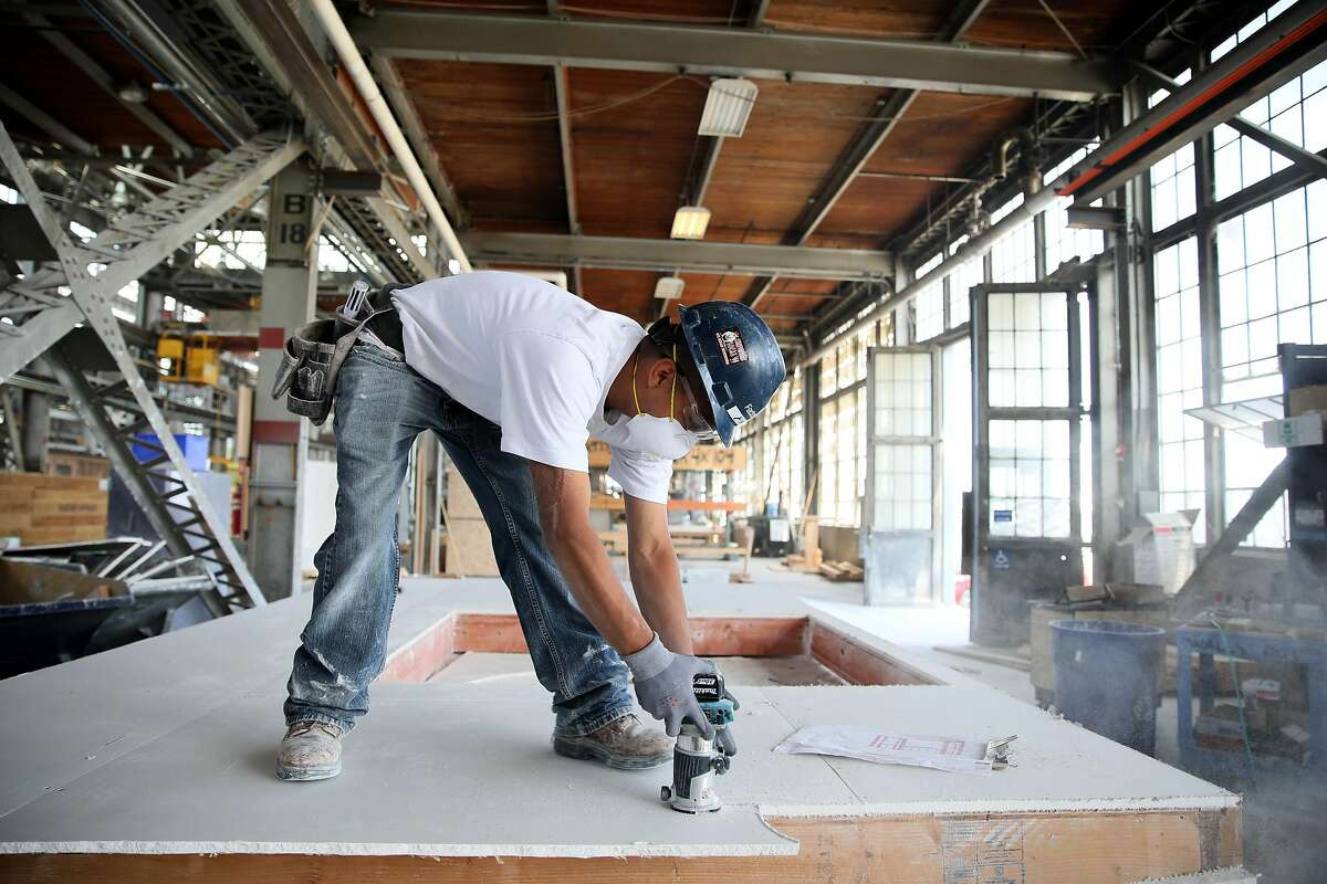 Chazz Arriaga works on a modular housing frame at the Factory_OS production factory in Vallejo.