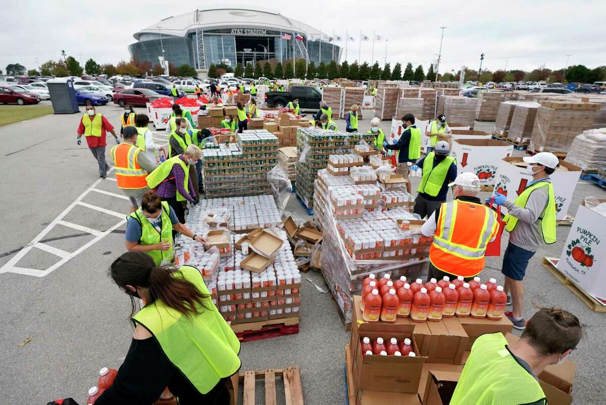 Volunteers build bags of dry goods in a parking lot outside of AT&T Stadium during a Tarrant Area Food Bank mobile pantry distribution event in Arlington, Texas, Friday, Nov. 20, 2020. Cars lined the surrounding streets around the home of the Dallas Cowboys and the nearby Texas Rangers Globe Life Field as Thanksgiving holiday food items were distributed to over 5,000 families.