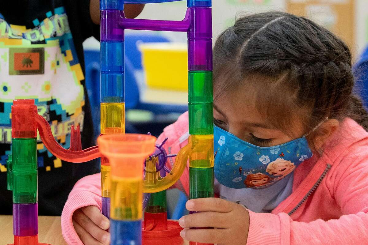 FILE -- A student wears a mask while building a marble racetrack in her Dinosaur pre-kindergarten class at Saint Vincent's Day Home in Oakland, Calif. Thursday, September 3, 2020.