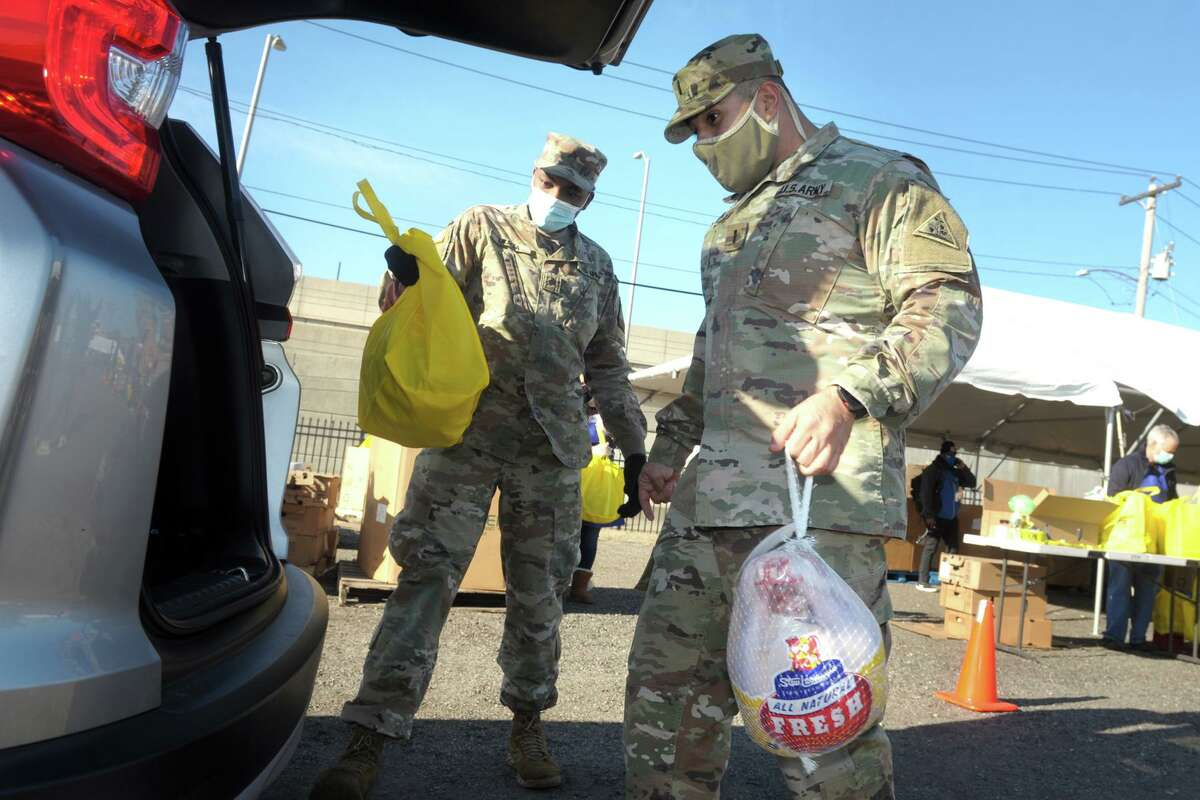 Connecticut National Guard Lt. Edwin Escobar, right, of Greenwich, and Sgt. Amos Muiga, of Middlebrook place a turkey and other Thanksgiving groceries into the hatchback of a waiting vehicle for the Bridgeport Rescue Mission's annual Great Thanksgiving Project in Bridgeport, Conn. Nov. 20, 2020.