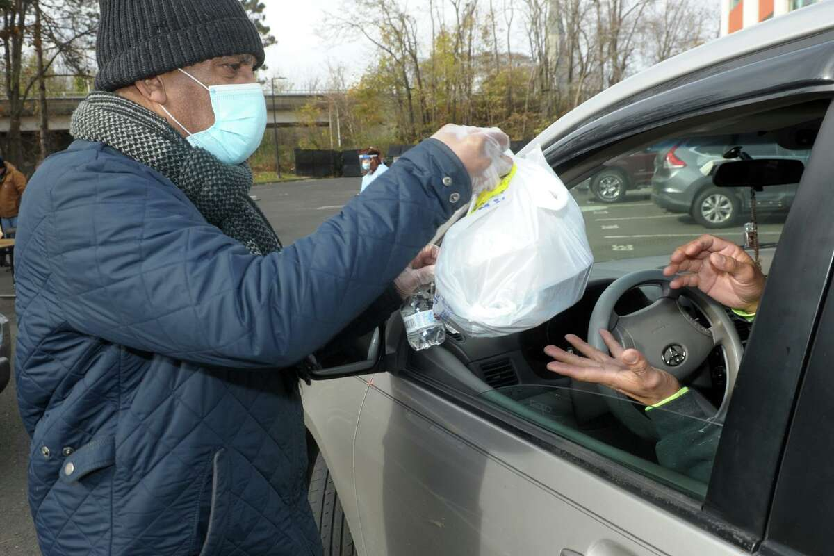 Lawrence Hudson from Career Resources delivers a boxed and bagged Thanksgiving meal to a waiting motorist during a food donation in Bridgeport, Conn. Nov. 19, 2020. The meals were provided by the Kennedy Center, and volunteers from Career Resources served the meals during the event.