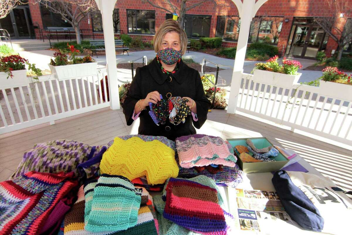 Sarah Moskowitz shows some of the masks and blankets she and other volunteers have made to be distributed to residents at The Towers as well as members of the community in New Haven, Conn., on Wednesday Nov. 18, 2020.