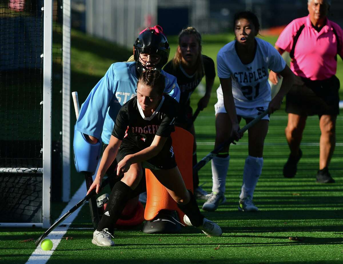 Staples High School Ella Williams looks over at Ridgefields #13 Mackenzie Peters tin their FCIAC Central field hockey championship game Tuesday, Novemver 10, 2020, in Westport, Conn.