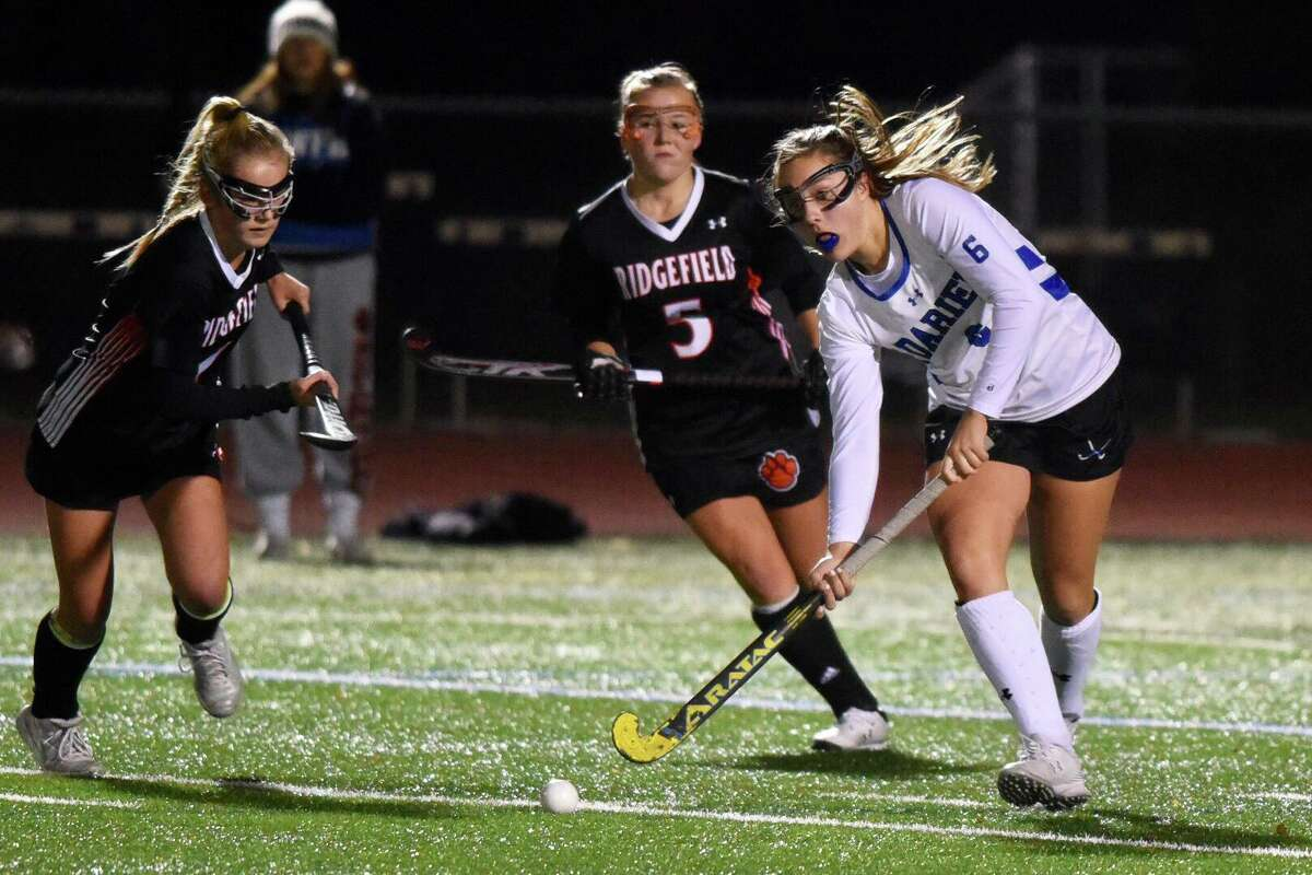 Darien's Maddie Hult (6) plays the ball with Ridgefield's Riley Peters (5) in pursuit during the CIAC Class L field hockey semifinals at Weston High School on Nov. 19, 2019.