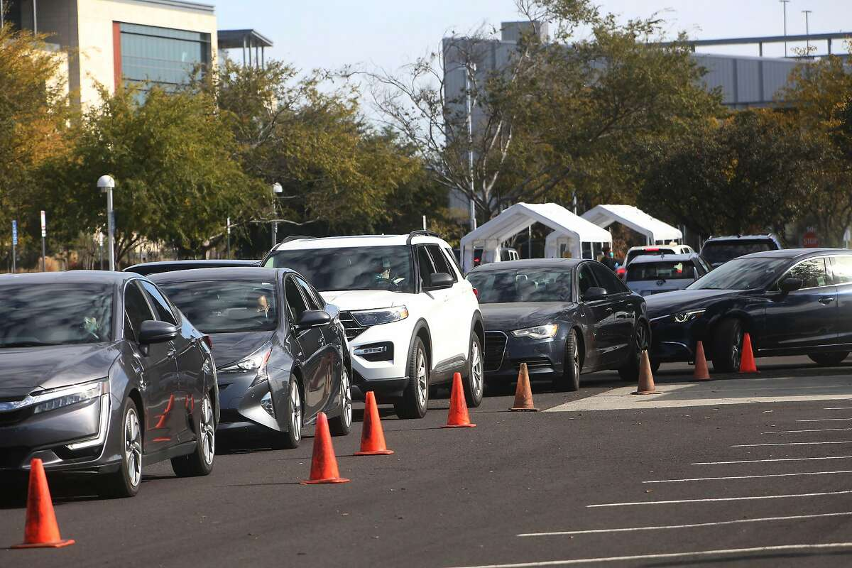 Cars lined up in a parking lot at a coronavirus testing site Redwood City. California is requiring employers to fund tests for employees if there is exposure on the job.