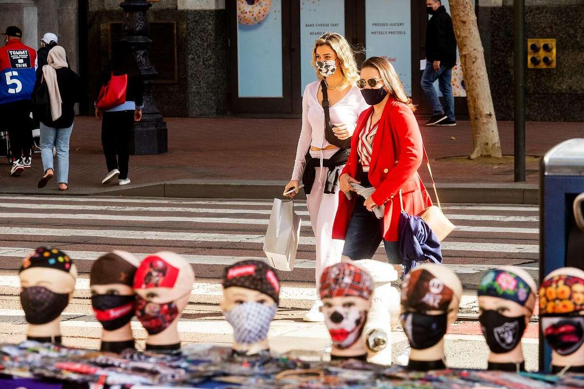 Masks line a vendor's display table on Market Street in San Francisco.