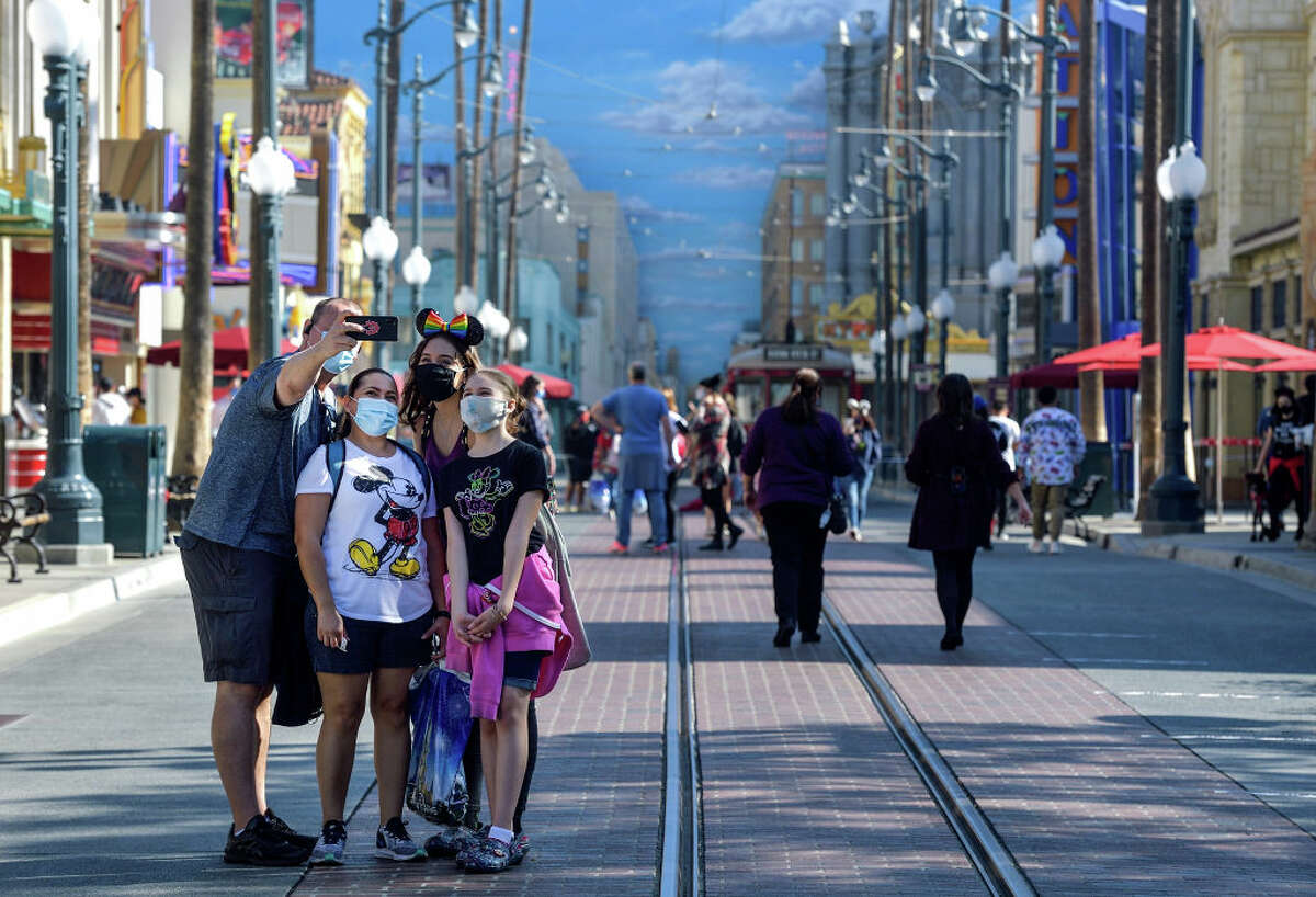 Kim Burgett, left, his wife, Ericka Prado, and their daughters Alyna Burgett and Rilye Burgett, pose for a selfie on Hollywood Boulevard in Hollywood Land inside Disney California Adventure Park in Anaheim, Calif., on Thursday, Nov. 19, 2020.