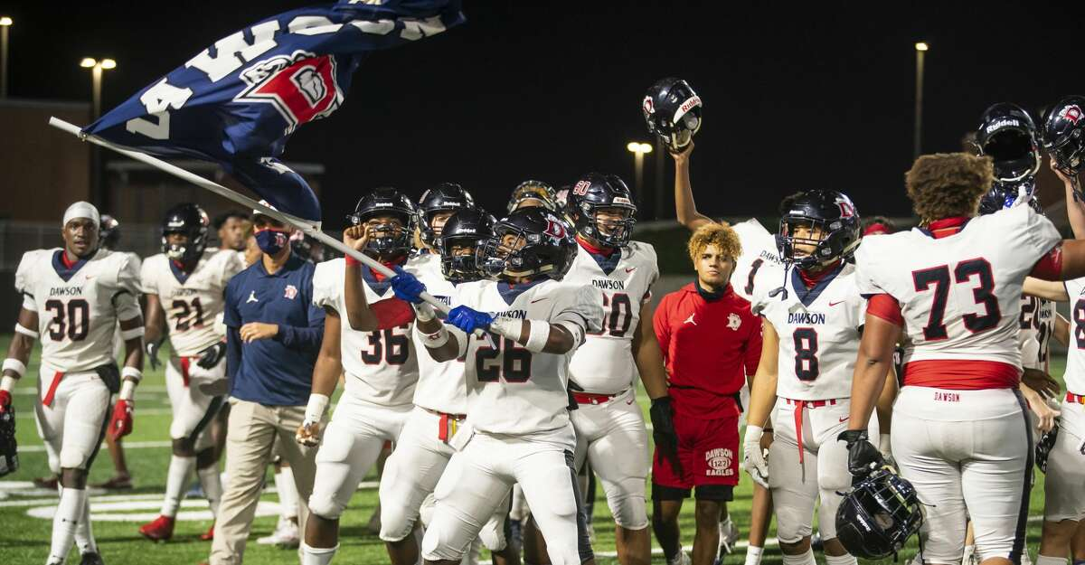 Dawson's Langston Nabors waves a flag as the team celebrates their overtime win during a game between Shadow Creek High School and Dawson High School on Friday, Nov. 20, 2020, at Freedom Field in Arcola, TX.