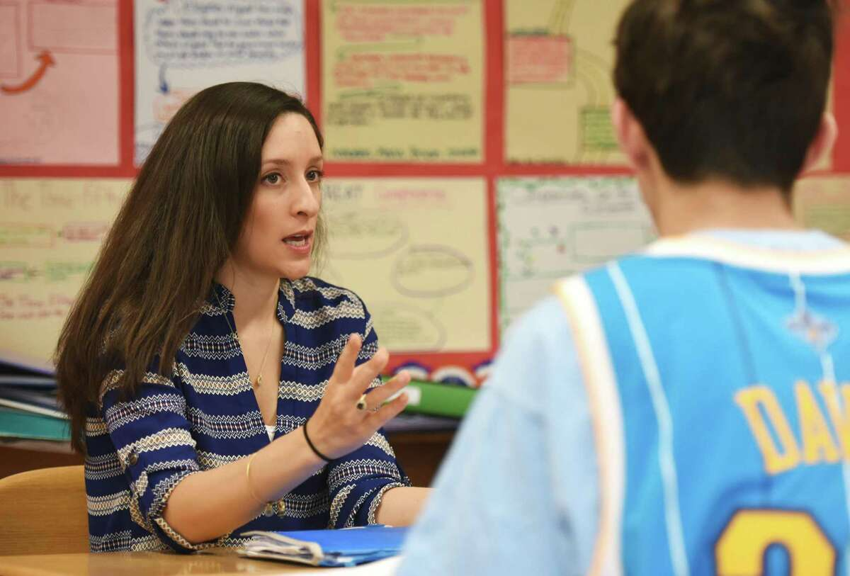 Teacher Diana Willie helps students in one of her eighth-grade social studies classes at Western Middle School in Greenwich, Conn. Wednesday, April 29, 2015.