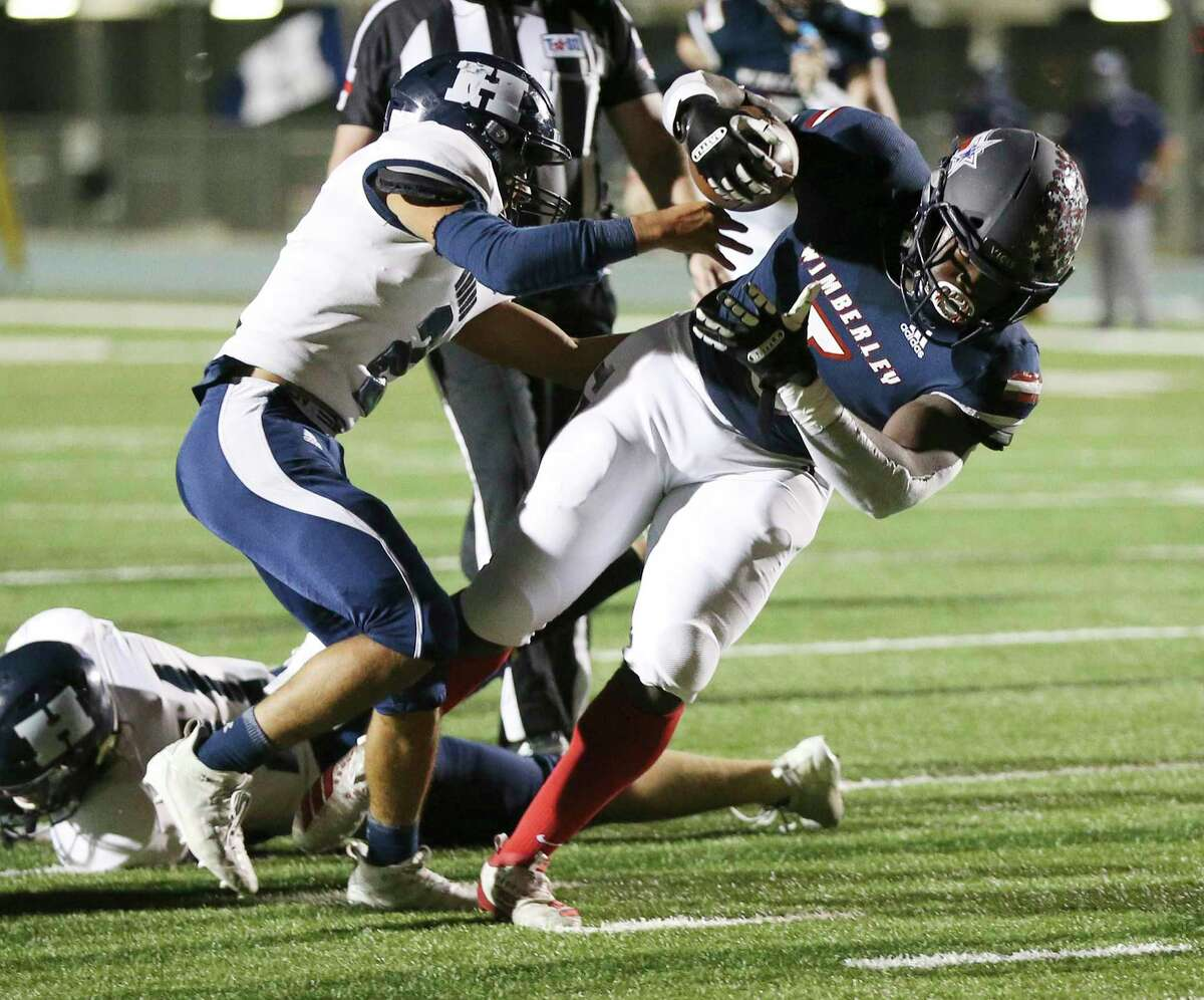 Wimberley's Moses Wray (05) fights off a tackle from Hondo's Aaron Ledesma (02) to score the game's first touchdown during their high school second round playoff football game at Southwest Legacy Stadium on Friday, Nov. 20, 2020.