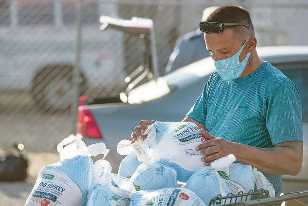 Volunteer Danny Lujan restocks a cart of frozen turkeys during a Thanksgiving giveaway.