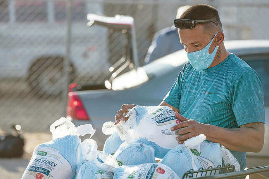 Volunteer Danny Lujan restocks a cart of frozen turkeys during a Thanksgiving giveaway. Photo: Eli Hartman   Odessa American (AP)