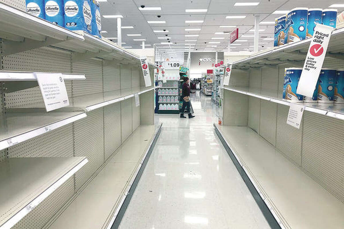 Shelves in the toilet paper aisle at a Target store sit empty in Vernon Hills. A surge of new coronavirus cases in the U.S. is sending people back to stores to stockpile again, leaving shelves bare and forcing retailers to put limits on purchases.
