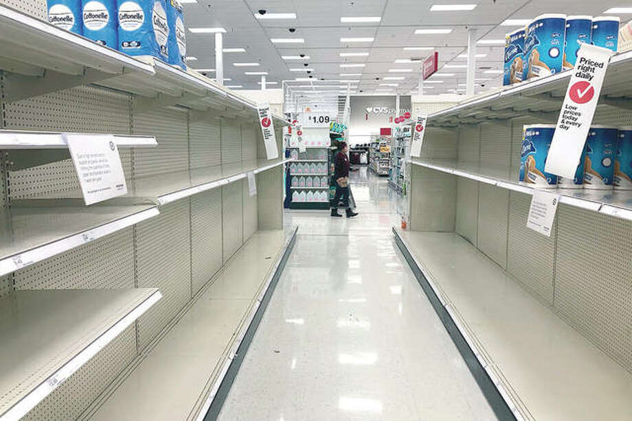 Shelves in the toilet paper aisle at a Target store sit empty in Vernon Hills. A surge of new coronavirus cases in the U.S. is sending people back to stores to stockpile again, leaving shelves bare and forcing retailers to put limits on purchases. Photo: Nam Y. Huh | AP