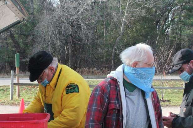 Max Matijczyk (center) waits at the DNR check station on Wednesday while wildlife biologist Pete Kailing examines his buck. (Pioneer photo/John Raffel)