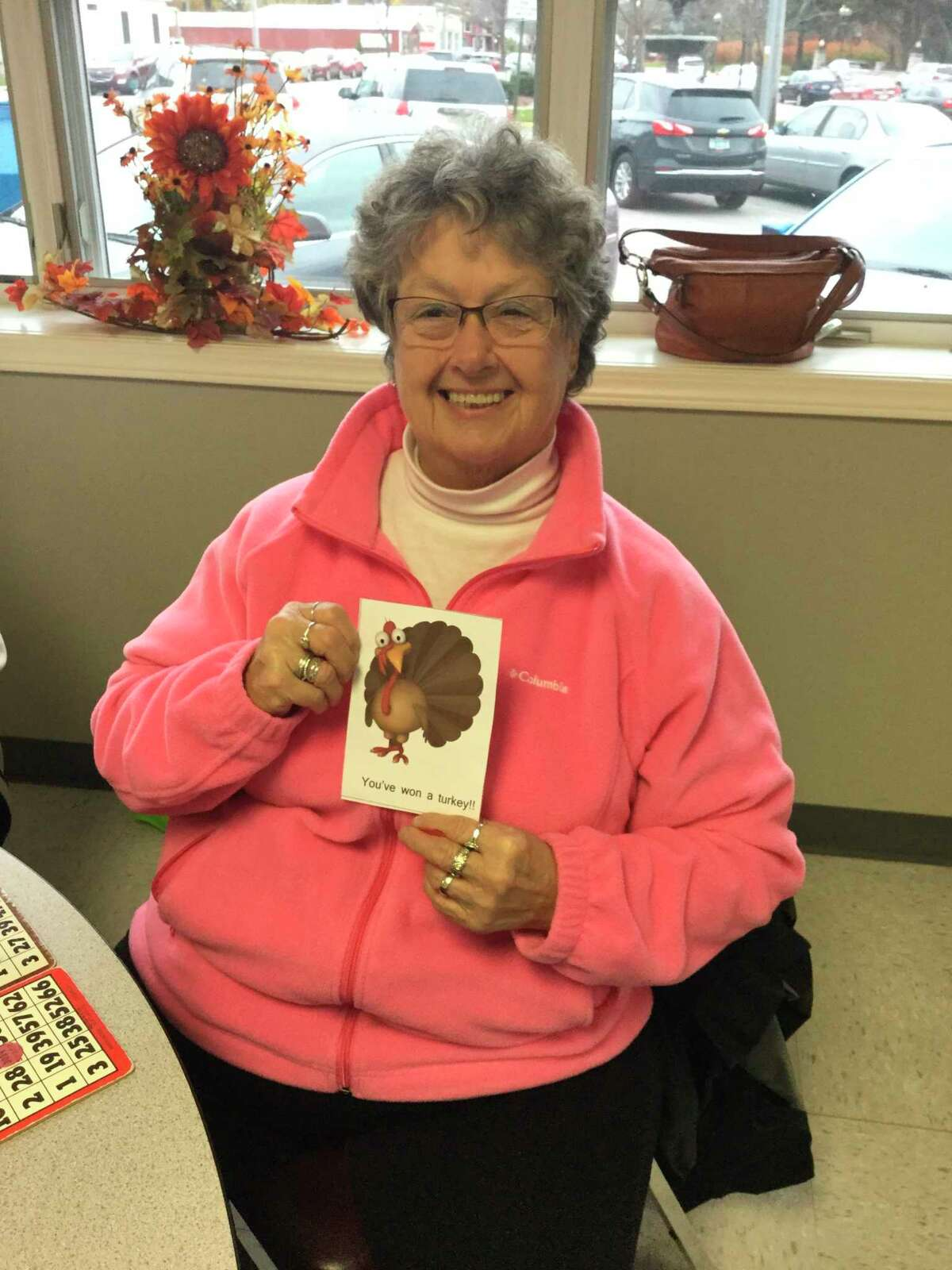 The Manistee County Council on Aging employees and volunteers forward to the time when everyone can gather again for fun activities. In Novembers past, volunteer Donna Kukla wins a turkey in a drawing during a weekly bingo day. (Courtesy Photo)