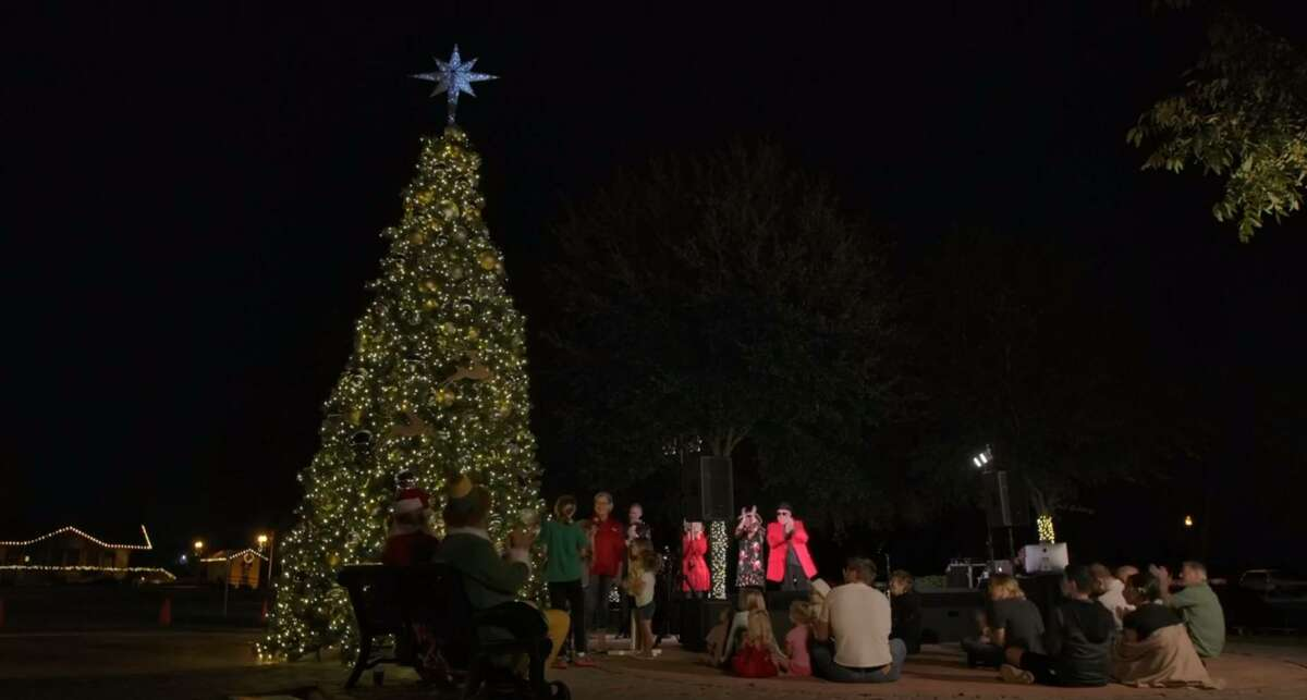 People cheer as Mayor Gretchen Fagan lights the tree during the annual Christmas tree lighting ceremony livestreamed virtually from Tomball on Nov. 20, 2020.