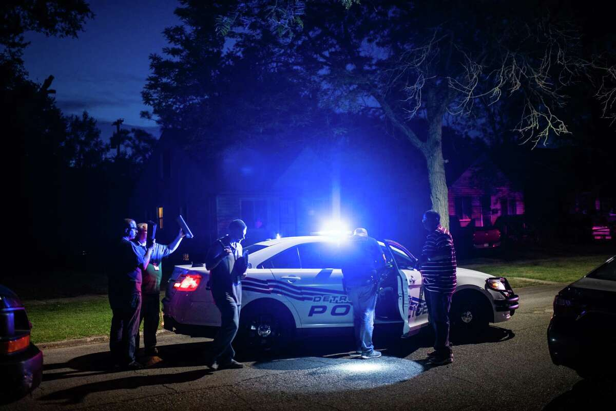 Detroit Police homicide detectives at the scene of a fatal shooting in 2018.