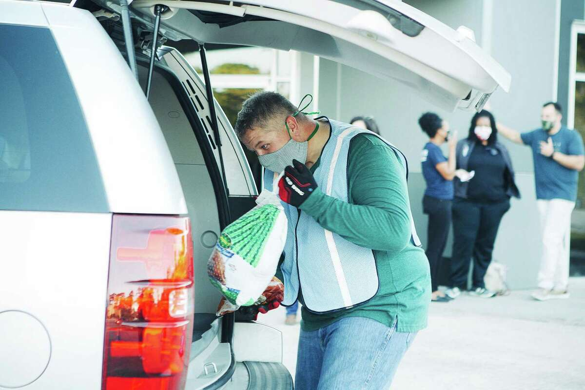 Jeff Keith loads a turkey into a family's car during the church's ThanksSending help for the needy in the community. It's the fifth year the church has opened their parking lot to assist families for the holidays.