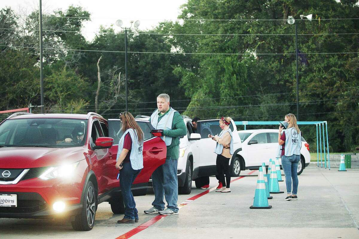 Jeff Keith and Gina Polston help deliver food to families in a line of cars at The MET Church on 13000 Jones Road last Thursday. The donations help needy families in their area for the holidays.