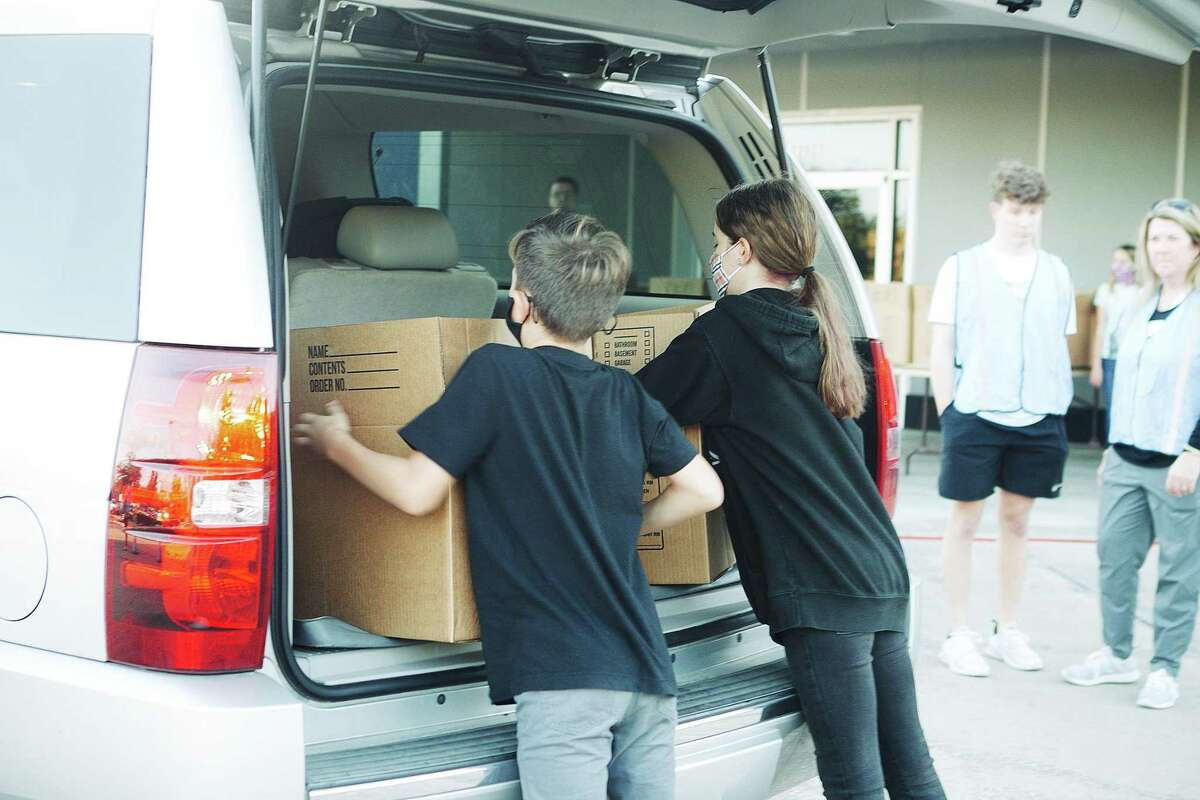 Jayden and Jackson Corthell help load meals into the trunks of waiting vehicles filled with needy families receiving welcome assistance for the Thanksgiving holiday.