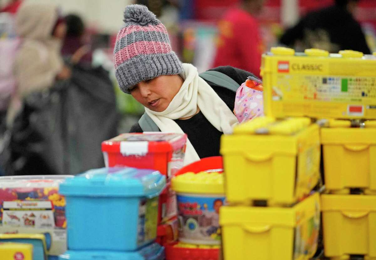 Amalia Gomez looks for toys for her two children during the Houston Children's Charity Annual Christmas Toy Distribution at George R. Brown Convention Center Friday, Dec. 20, 2019, in Houston. The Houston Children's Charity partnering with the U.S. Marines' Toys for Tots program and the Houston First Corporation will give an estimated 80,000 toys to the parents of over 20,000 children in need.