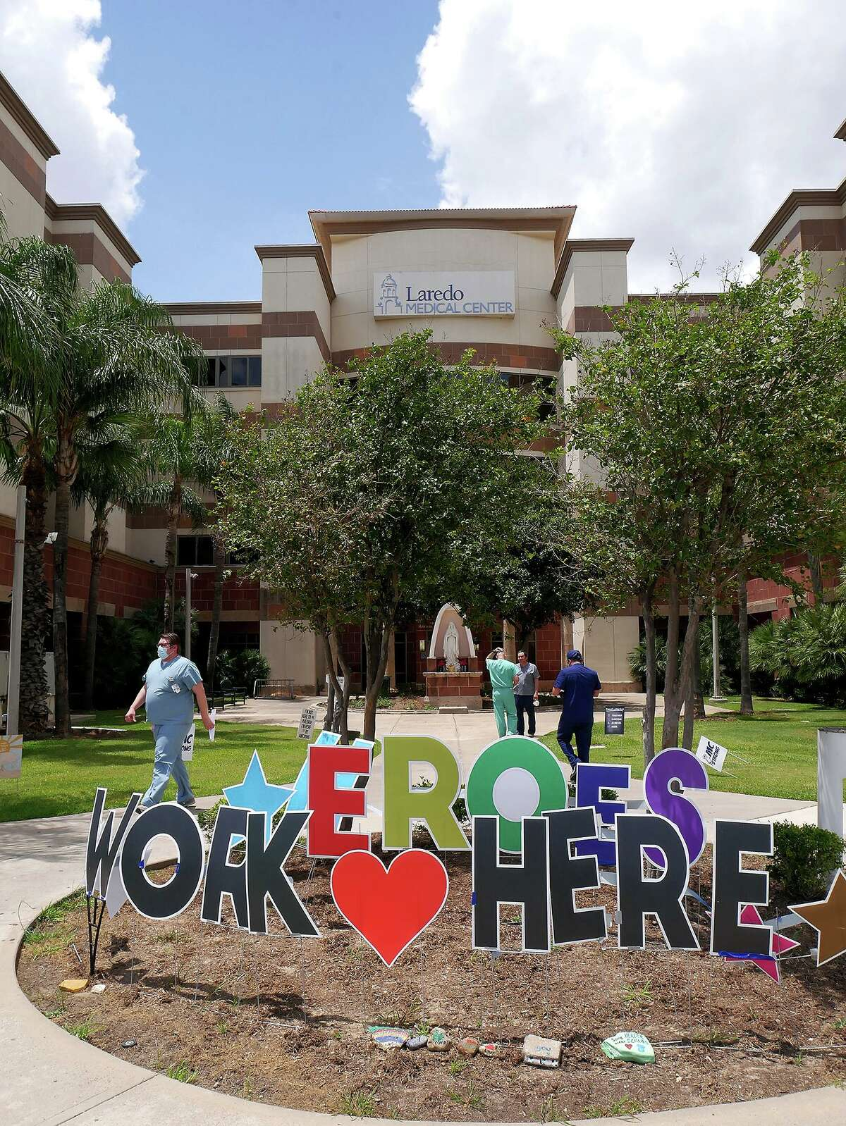 """A """"Heroes Work Here"""" sign sits outside Laredo Medical Center on May 11, 2020 as workers walk in and out of the facility. Recently, some recently departed staff discussed why many are leaving the area in favor of state positions, which they describe as having more pay and less stress."""