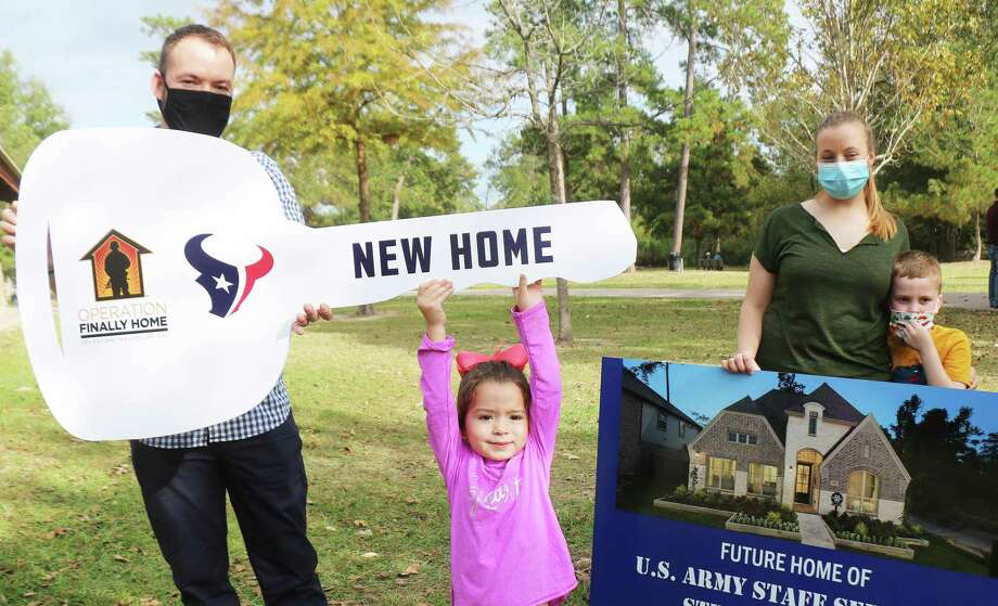 Three-year-old Mrazy helps hold up the ceremonial key to her new home at the surprise unveiling at Meyer Park on Friday. Her daddy, SSG E-6 Stephen Netzley, left, is joined by his sister Amber Pace and her son Michael. Photo: David Taylor / Staff Photographer