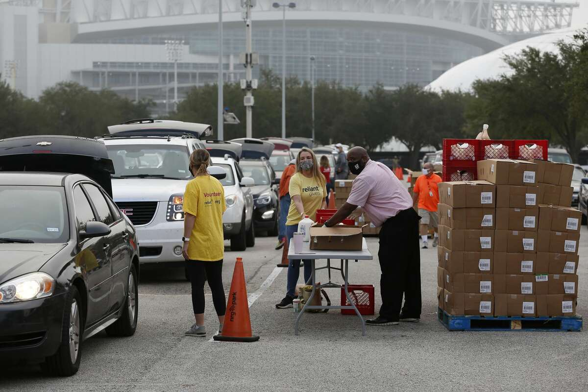 Long lines of cars await their turn to receive free food during the H-E-B Family Thanksgiving Distribution at NRG Stadium Saturday, Nov. 21, 2020, in Houston.
