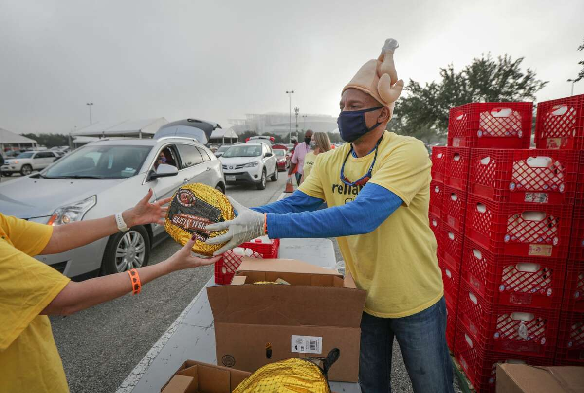 Reliant employee, Sidney Evan hands out frozen turkeys during the H-E-B Family Thanksgiving Distribution at NRG Stadium Saturday, Nov. 21, 2020, in Houston.