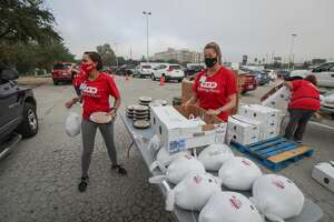 H-E-B Lacey Dalcouk Salas (l) and Julie Lambert deliver pies and turkeys to a vehicles during the H-E-B Family Thanksgiving Distribution at NRG Stadium Saturday, Nov. 21, 2020, in Houston