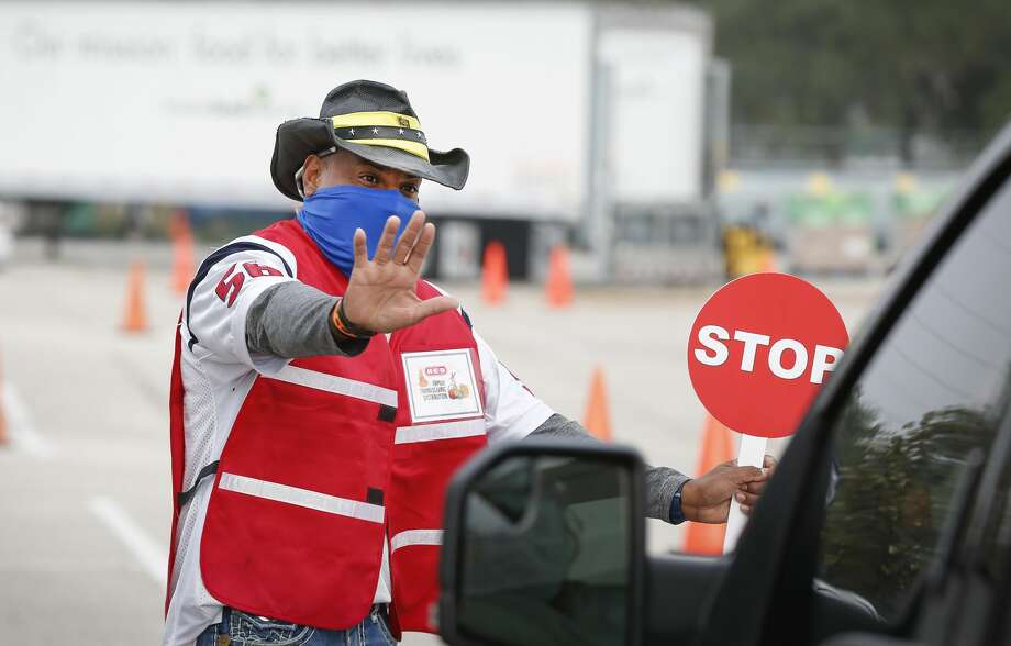 Alfredo Guadamuz jokes with drivers as they made their way through the pick-up lines during the H-E-B Family Thanksgiving Distribution at NRG Stadium Saturday, Nov. 21, 2020, in Houston. Photo: Steve Gonzales/Staff Photographer / © 2020 Houston Chronicle