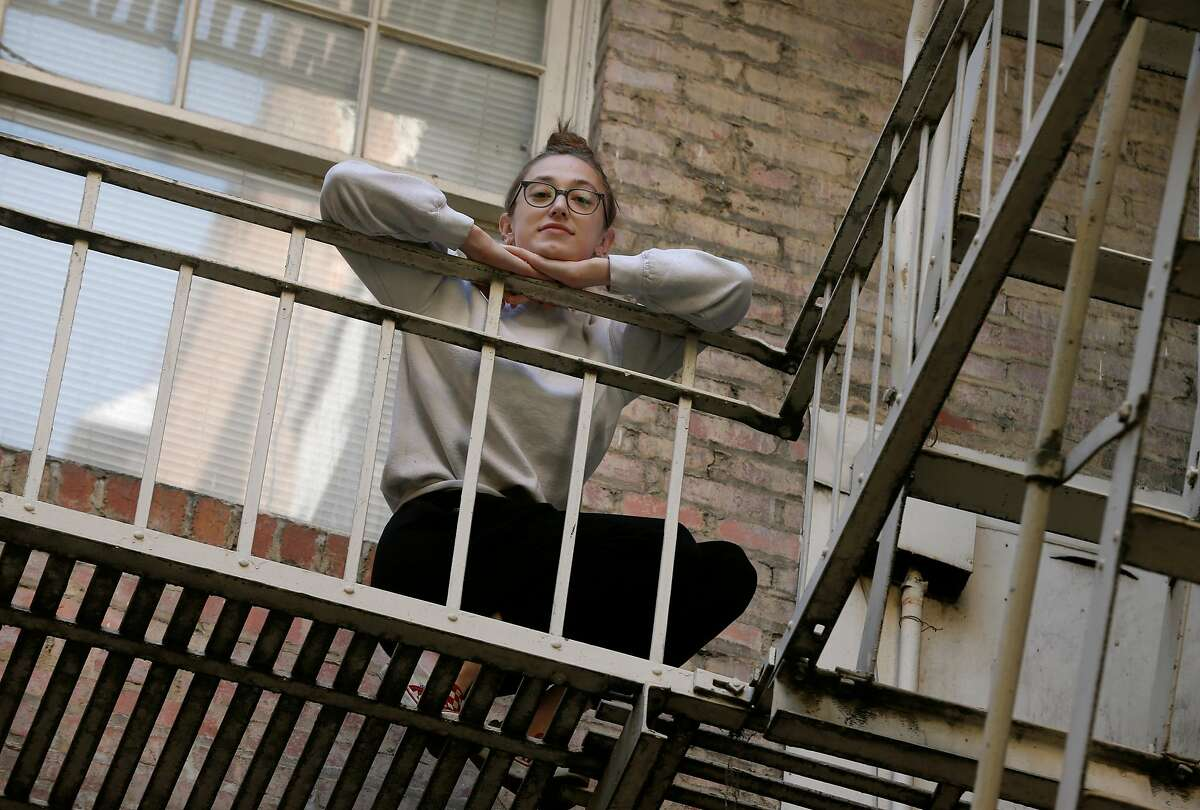 Becca Camping, who is self-quarantining after testing positive for the coronavirus, stands on the fire escape outside her Tenderloin apartment. Camping, who works at a barbecue restaurant, often serves people who are unmasked the whole time.