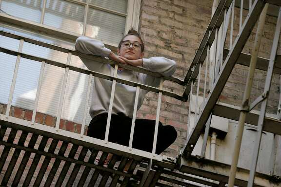 Becca Camping stands on the fire escape outside her third floor apartment in San Francisco, Calif. on Saturday, Nov. 21, 2020. Camping is self-quarantining after testing positive for the COVID-19 coronavirus.