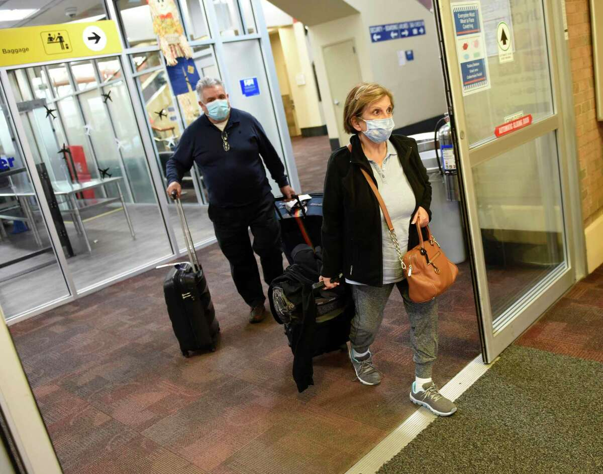 Travelers wear masks as the exit the Westchester County Airport in White Plains, N.Y. Thursday,. Westchester County Airport has taken many sanitary precautions and implemented mandatory masks to decrease the risk of contracting COVID-19 in its facilities.