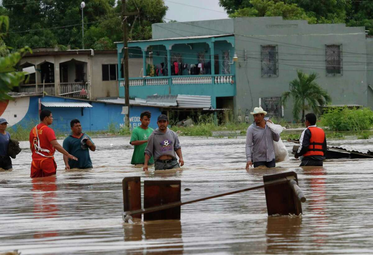 Men wade through a street flooded after the passing of Hurricane Iota in La Lima, Honduras, Wednesday, Nov. 18, 2020. Iota flooded stretches of Honduras still underwater from Hurricane Eta, after it hit Nicaragua Monday evening as a Category 4 hurricane and weakened as it moved across Central America, dissipating over El Salvador early Wednesday. (AP Photo/Delmer Martinez)
